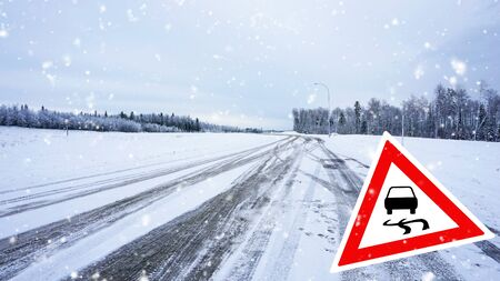 Snow covered road, winter driving with road sign - slippery road