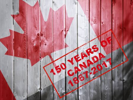 canada stamp: 150 years of Canada 1867-2017 red stamp words on wooden background with Canadian flag