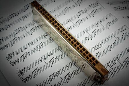 harmonica: A harmonica on music sheets background Stock Photo