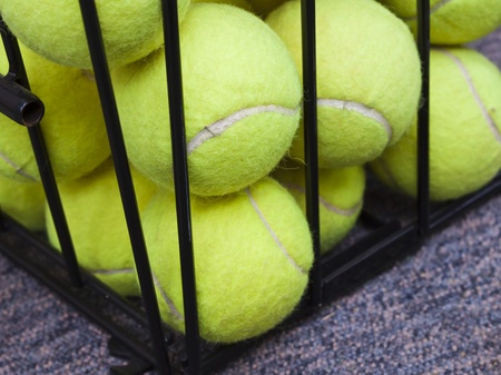 Some tennis balls stored in steel baskets photo