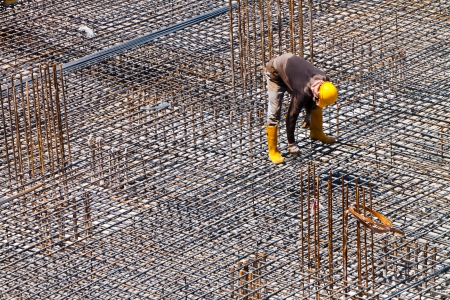 on rebar: A worker is doing a final inspection of the floor reinforcement Stock Photo