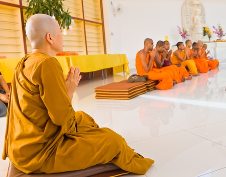 chanting: A Buddhist nun listening to chanting given by monks