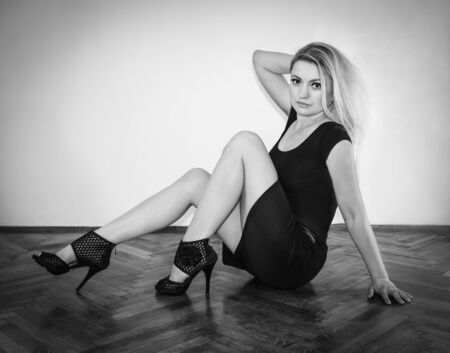 Blonde in heels sitting on the floor Banque d'images
