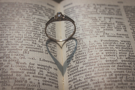 Ring and heart shadow around the word love in dictionary