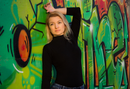 Blond woman in black shirt standing by the wall with graffiti