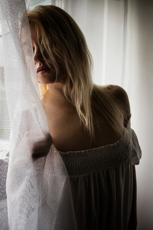 Blonde behind curtain