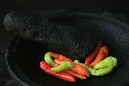 Mortar contains colorful chilies, ready to be pulverized and processed into chili sauce and other dishes. Reklamní fotografie