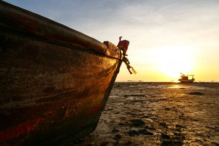 orenge: The fishing boat on the beach in sunset