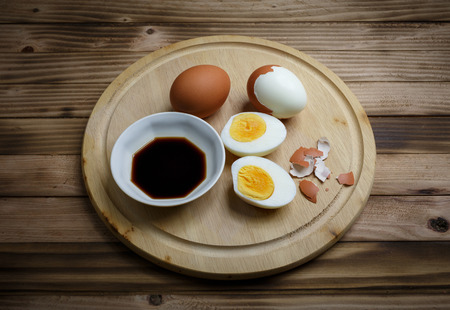 sause: Boiled egg, cooked wiht Soy sause on  the plate wood background Stock Photo