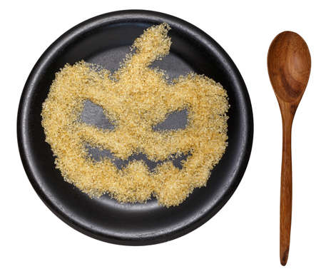haunting: Halloween Pumpkin sugar on black dish  on white background isolated