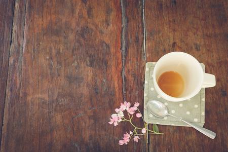 afternoon cafe: Café de la tarde relajarse, vaciar una taza de café con la flor en la mesa de madera de época Foto de archivo