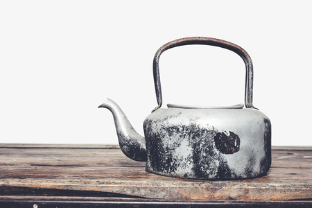 stovetop: Retro old kettle on the wood table and white background, vintage Stock Photo