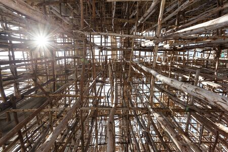 Wood Scaffolding on a construction site of a new building with ant eye view and sun light flar
