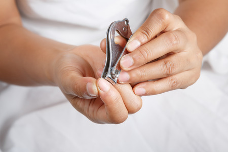 woman hand cutting fingernails with herself Stock Photo