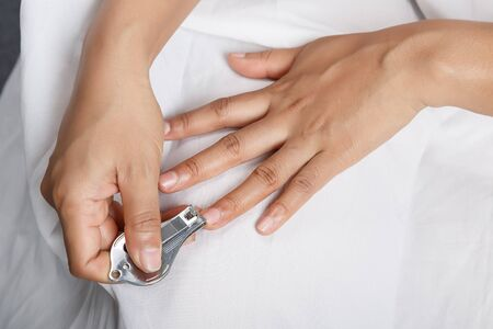 herself: woman hand cutting fingernails with herself Stock Photo