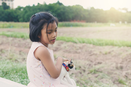and plot: A cute girl sitting and her playing a cat on planting plot