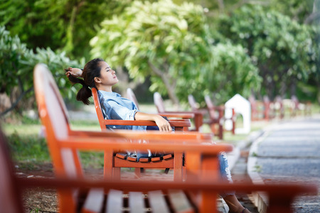 Woman  wearing jeans and a denim jacket. She relax in the holiday and her lifestyle at the public park