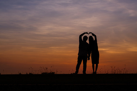 Silhouette man and woman with beautiful the sky at sunset. Background, he and she inside sweetheart, They were both playing and happy. Stock Photo