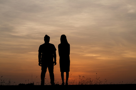 Silhouette man and woman with beautiful the sky at sunset. Background, he and she inside sweetheart