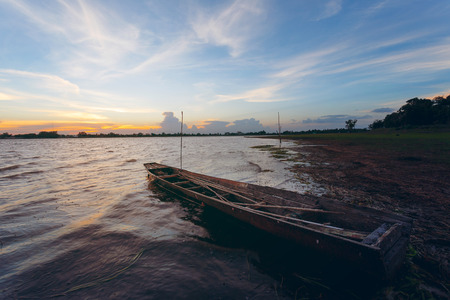 pus: Vintage Sunset and fishing boat in reservoir with wave and wind Archivio Fotografico