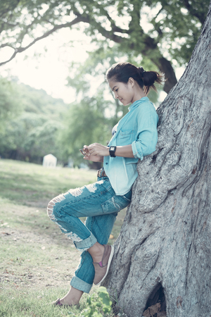 leaned: Woman  wearing jeans and a denim jacket. She relax in the holiday and her lifestyle at the public park. She leaned against a tree
