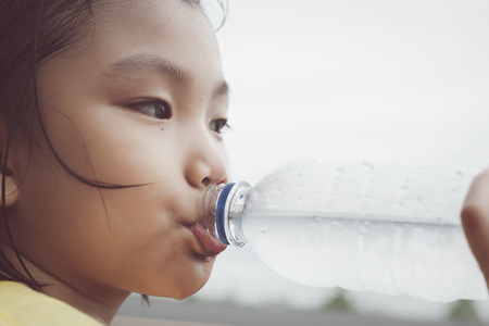 thirst: Cute girl is drinking water from plastic bottle. Clean water will help solve the thirst for her. Stock Photo