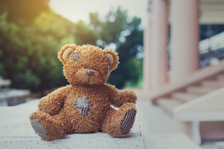 Cute old brown teddy bear sitting outdoors background.