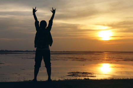 Silhouette woman lifestyle relax at sunset and her raise hands to communicate love Stock Photo