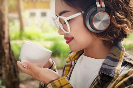 lifestyle Young women relax Private By drinking coffee and listening to music with Wireless Headphones