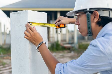 Male architect measuring house wall post At the village construction work