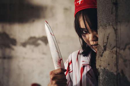 Nurse uniform killer Hold the knife and peek At an abandoned hospital