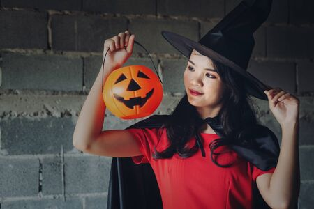 The witch girl dress up Halloween Party And she holds a pumpkin in her hand Banque d'images