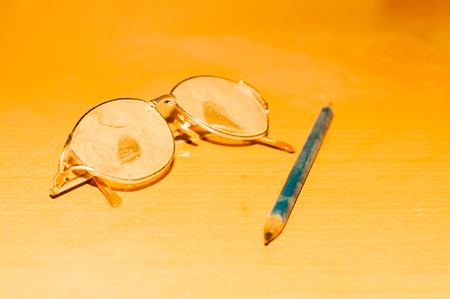 blinkers: Old glasses and pencil filled with dust on the table
