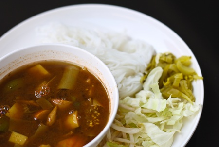 pla: Tai curry noodles with vegetables on a white plate. Stock Photo