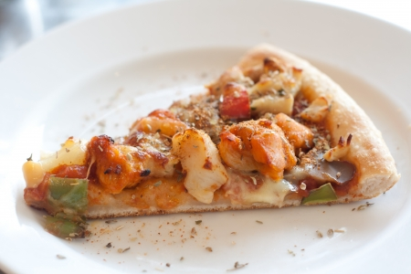 Pizza with sausage, ham, chicken, bell pepper, pineapple on a white plate  photo