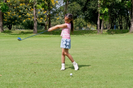Girl playing golf, T-off on green grass.