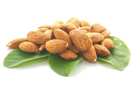 Almonds on green leaf and white background  photo
