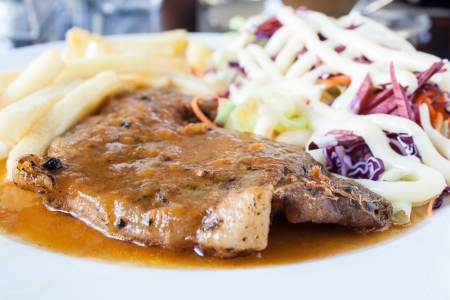 Pork steak with french fries and salad on a white plate  photo