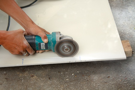 Workers are using tools for cutting tile  photo