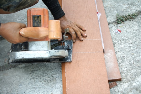Workers are using a circular saw to cut wood  photo