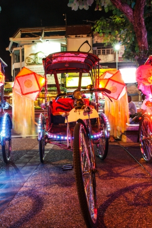 Thailand on a tricycle adorned with lamps. photo