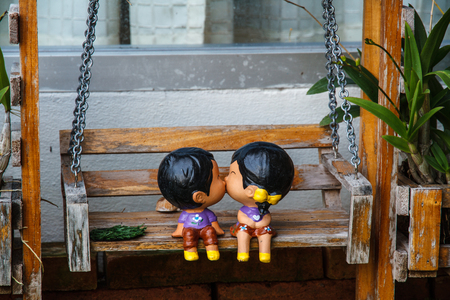 woman hanging toy: Clay dolls man and woman kiss on swing. Stock Photo