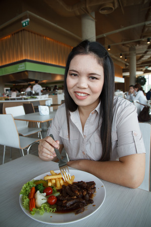Woman eating steak in a food center. photo