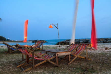 Seating for dinner on the beach in the evening after sunset. photo