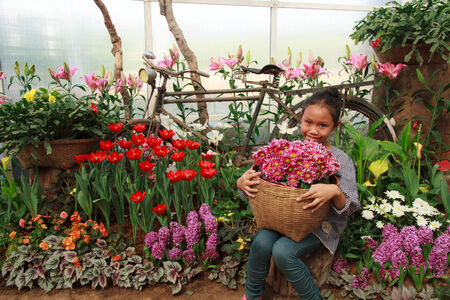 Young Asian woman sitting holding a basket of flowers. photo