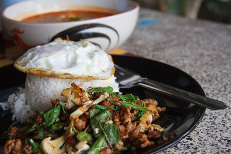 Fried basil pork with rice and eggs, spicy Thai food  photo