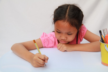 Girl writing a book with a pencil. Stock Photo - 25916919