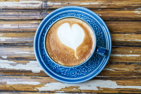 Hot coffee drawing hearts in blue glass. photo