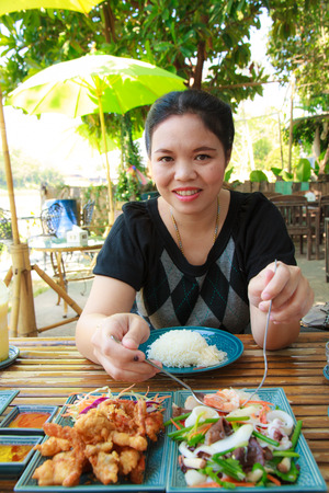 Woman eating lunch with vermicelli salad and crab fried in restaurant. photo