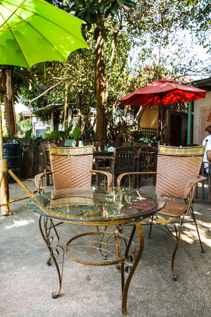 dining table and chairs: Dining table glass and two chairs outside in restaurant.